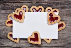 Empty paper with many heart cookies on rustic table Royalty Free Stock Photography