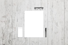 Empty paper and mobile phone on office desk. Top view with glasses and pen beside stock photos