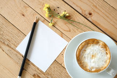 Empty paper note and a cup of cappuccino coffee. White empty paper note and pencil and yellow flowers with the cup of cappuccino coffee. There are on wooden Stock Photo