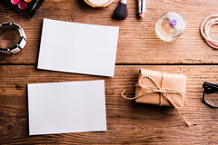 Empty paper notes, little package and make up products. Stock Photos