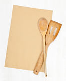 Recipe background. Empty paper for recipe with wooden cooking utensils on kitchen table Royalty Free Stock Photography