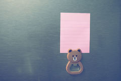 Empty paper sheet on refrigerator door. Note paper with magnetic bear Royalty Free Stock Photography