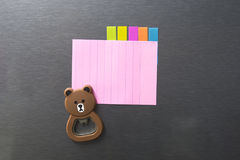Empty paper sheet on refrigerator door. Note paper with magnetic bear Stock Images