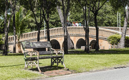 Empty Park bench in the background the stone bridge at city Park Royalty Free Stock Photo
