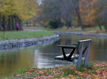 Empty park bench in the fall. An empty park bench in the fall beside a river Stock Photo