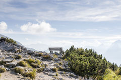 Empty park bench in high mountains Stock Photo