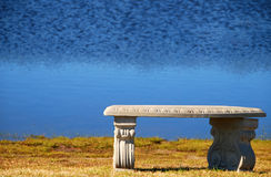 Empty Park Bench by Lake. Inviting empty park bench at water's edge of lake Royalty Free Stock Image