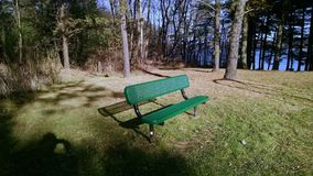 Empty. Park bench located beside a lake in the setting sunshine Stock Photos