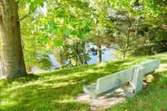 Empty park bench seat overlooking lake. Empty park beanch seat overlooking lake through trees Royalty Free Stock Photos