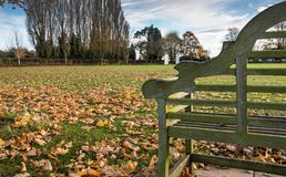 Empty park bench seen in a public park, close to a football pitch, seen in winter. stock images