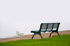 Empty park bench, wet from the rain on the shore of a misty lake Royalty Free Stock Images