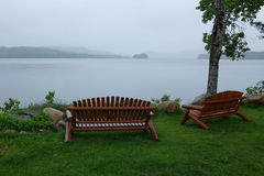 Empty park benches by the lake in rain Stock Images