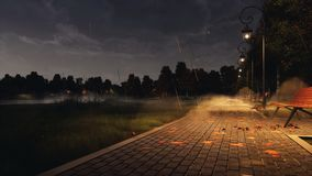 Empty park walkway at misty autumn night with rain. Pavement walkway lit by street lights with empty benches and fallen autumn leaves in a city park at dark royalty free stock images