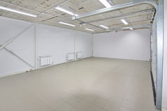 Empty parking garage, warehouse interior with large white gates and gray tile floor Stock Photo