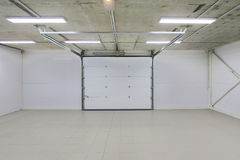 Empty parking garage, warehouse interior with large white gates and gray tile floor Royalty Free Stock Photos