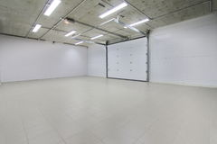 Empty parking garage, warehouse interior with large white gates and gray tile floor Royalty Free Stock Image