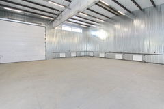 Empty parking garage, warehouse interior with large white gates and windows inside Stock Image