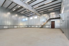 Empty parking garage, warehouse interior with large white gates and windows inside Stock Photo