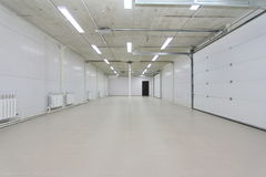 Empty parking garage, warehouse interior with large white gates and windows inside Royalty Free Stock Photo