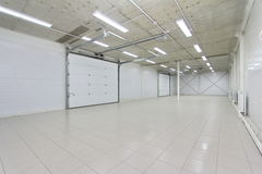 Empty parking garage, warehouse interior with large white gates and windows inside Stock Images