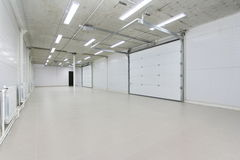 Empty parking garage, warehouse interior with large white gates and windows inside Royalty Free Stock Image