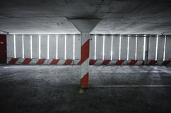 Empty parking garage. With white and red pillar and grey stone floor Royalty Free Stock Images