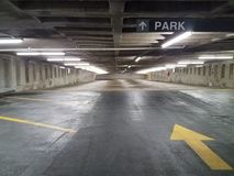 Empty parking garage with yellow arrow. Empty parking garage with black asphalt and yellow arrow royalty free stock photography