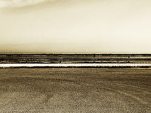 Empty parking with guardrail, grainy sepia hue. A detail of an empty parking with a guardrail just in the middle of it, a cloudy sky in the background, grainy Royalty Free Stock Photo