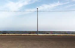 Empty parking with lamppost. An overall view of an empty parking with a single lamppost just in the middle of it, a cloudy sky in the background, landscape cut royalty free stock photos