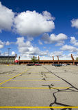 Empty parking lot. An empty parking lot scene with white clouds and blue sky Royalty Free Stock Image