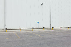 Empty parking lot. With enumerated parking spots and parking sign in front of white wall Stock Images