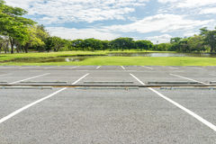 Empty parking lot against green lawn. In city park Royalty Free Stock Images
