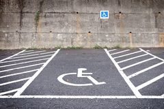 Empty parking lot with disabled parking sign on road. Stock Photos