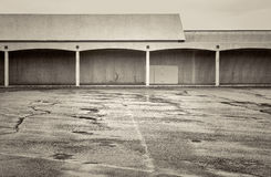 Empty parking lot of a shut down mall. Rain over empty parking lot of a shut down mall, black and white platinum toned image Stock Photography