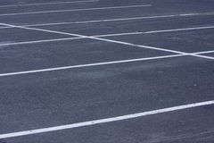Empty parking lot with white lines. Empty parking lot with rough, cracked asphalt pavement and white lines Royalty Free Stock Images