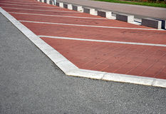 Empty parking lot. With white lines and a bicycle trail in the background Royalty Free Stock Photo