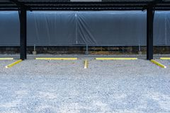 Empty parking lot with yellow car stops. At gravel floor Stock Photography