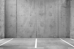 Empty Parking Lots in a Garage. Several empty parking lots in an open garage with concrete wall royalty free stock image