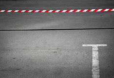 Empty parking place and prohibiting tape. Abstract minimal background with empty parking place and prohibiting red and white striped tape Stock Image