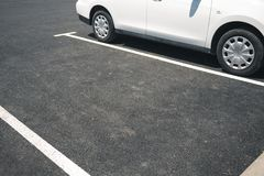 Empty parking place on a sunny day. White car parked next to an empty parking space. Parking with parked cars in sunny weather. white car parked on the street stock image