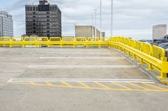 Empty Parking Spaces at the Top of a Multi-storey Car Park. Empty Parking Spaces Surrounded by a Yellow Crash Barrier at the Top Level of a Parking Garage stock photo