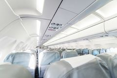 An empty passenger airliner. Commercial aircraft cabin with rows. Of grey seats down the aisle. Vacation destinations concept Stock Photography