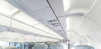 An empty passenger airliner. Commercial aircraft cabin with rows. Of grey seats down the aisle. Vacation destinations concept Royalty Free Stock Photos