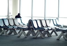 Empty passenger waiting seats in lounge after check-in next to air plane gate Royalty Free Stock Image