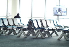 Empty passenger waiting seats in lounge after check-in next to air plane gate Royalty Free Stock Photography