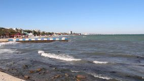 Empty pebble beach in Koktebel in autumn in Crimea. Empty pebble beach in Koktebel in the Crimea in mid-October. In the clear sunny weather, small waves runs stock video footage
