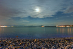 Empty pebble beach at night illuminated by the moonlight Royalty Free Stock Photography