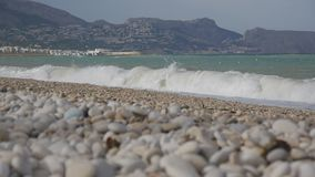 Empty pebble beach and waves of the stormy sea. Empty pebble beach and waves of the stormy sea stock footage