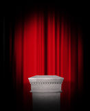 Empty pedestal display on red curtain. Empty pedestal display with spotlight in front of red stage curtain royalty free stock photo