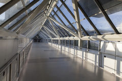 An empty pedestrian bridge at an airport is light by early morni Stock Photography